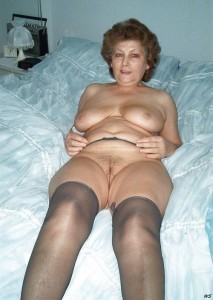 Julie a 79 old wicked FLASHING GRANNY posing in her bed and wearing sexy gray holdups
