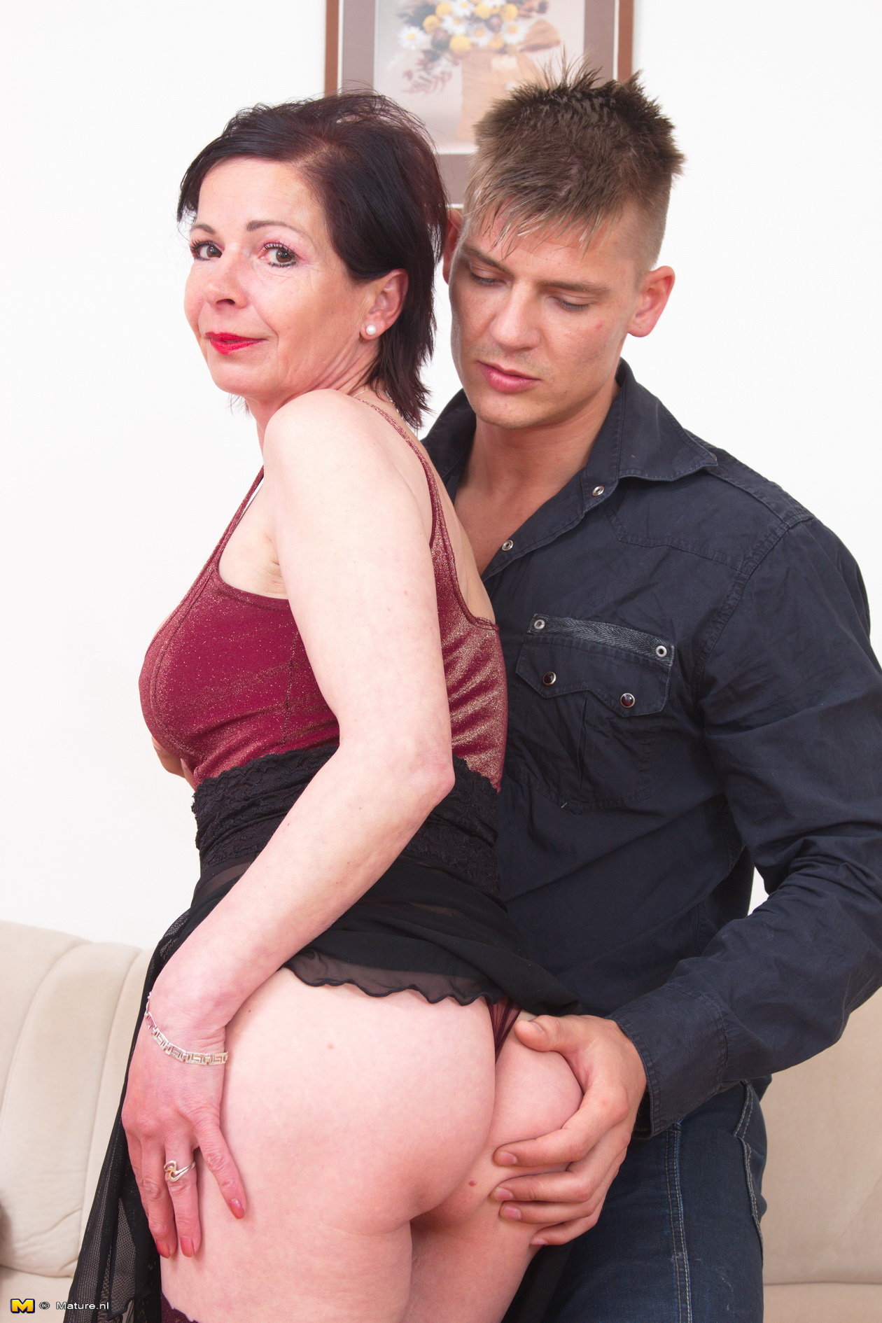 older experienced woman shows a young boy how to make love