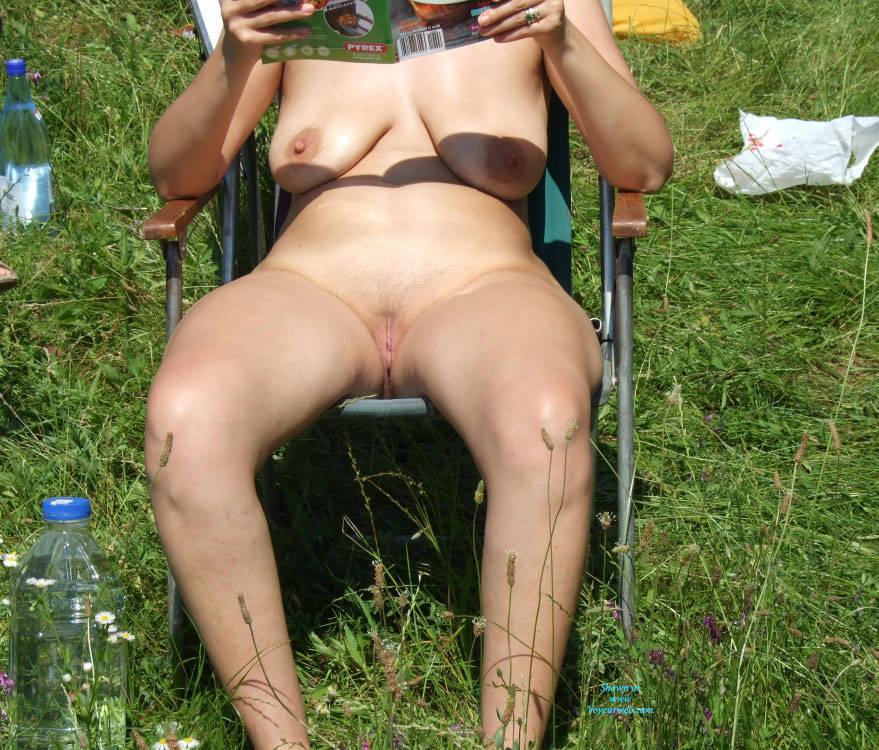 horny granny sitting naked in the garden and reading a cooking magazine