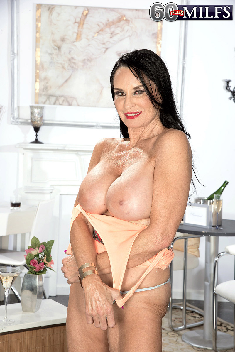 busty black haired granny pornstar rita daniels preparing a drink for the night and flashing her wonderful tits